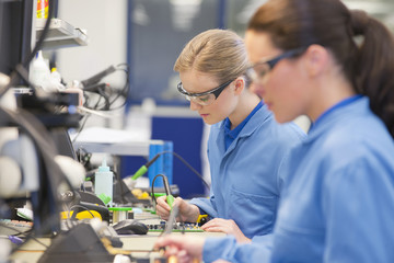 Technicians soldering circuit boards on production line in manufacturing plant