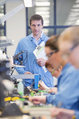 Portrait of smiling supervisor watching technicians solder circuit boards on production line in manufacturing plant