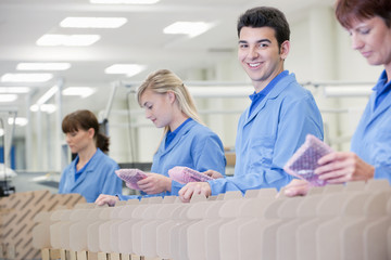 Portrait of smiling worker packing products in manufacturing plant