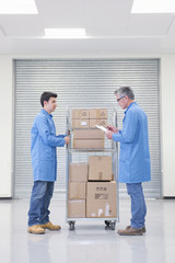 Workers with cart of cardboard boxes and clipboard in warehouse