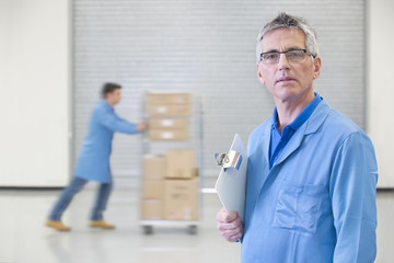 Portrait of serious worker with clipboard in warehouse