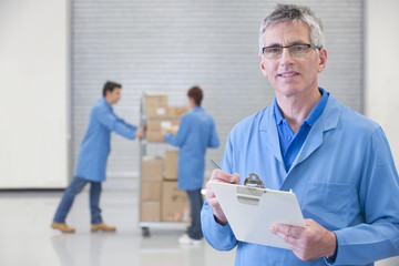 Portrait of smiling worker with clipboard in warehouse