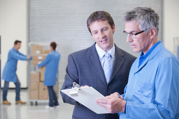Businessman and worker with clipboard in warehouse