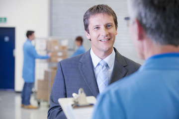 Smiling businessman talking to worker with clipboard in warehouse