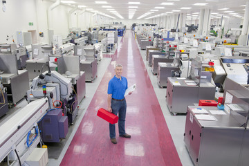 Portrait of engineer with clipboard and toolbox in aisle of manufacturing plant