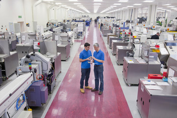 Engineers examining machine part in aisle of manufacturing plant