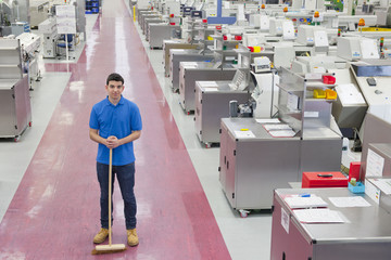 Portrait of smiling worker with broom in aisle of manufacturing plant