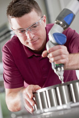 Technician using measurement probe on assembly line in steel bearing manufacturing plant