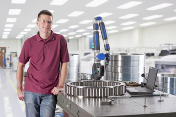 Portrait of smiling technician standing next to measurement probe in steel bearing manufacturing plant