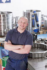Portrait of smiling technician in steel bearing manufacturing plant