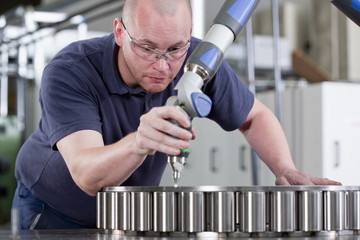 Technician using measurement probe in steel bearing manufacturing plant