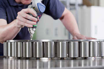 Close up of technician using measurement probe in steel bearing manufacturing plant