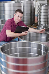 Technician checking steel roller bearing inventory in warehouse