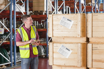 Smiling worker with digital tablet checking crates in warehouse