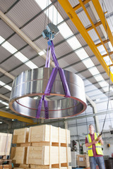 Worker moving steel roller bearing on hoist in manufacturing plant