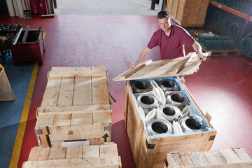 Worker packing steel roller bearings in crate in warehouse