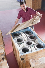 Man packing steel roller bearings in crate in warehouse