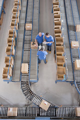 Workers meeting among boxes on conveyor belts in distribution warehouse