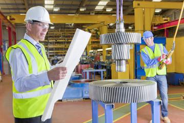 Engineer inspecting blueprints near gear wheels in factory