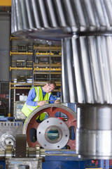 Worker inspecting gear wheels in factory