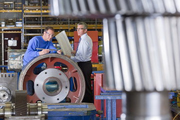 Engineer and worker inspecting gear wheels in factory
