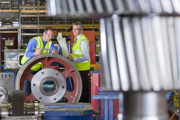 Engineers inspecting gear wheels in factory