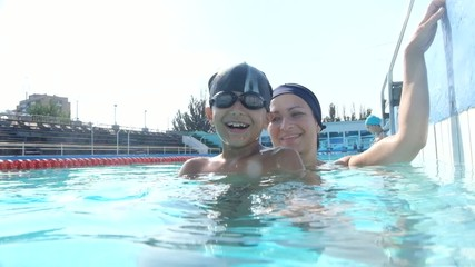 Happy pretty woman with her son in swimming pool looking happy