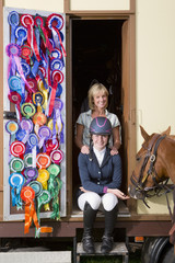 Portrait of smiling mother and daughter in equestrian uniform with horse in doorway of trailer with rosettes covering door