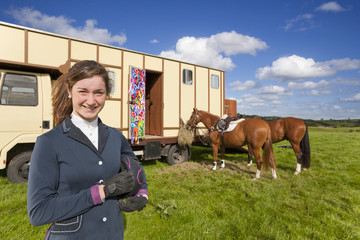 Portrait of smiling girl in equestrian uniform near horses and trailer in field