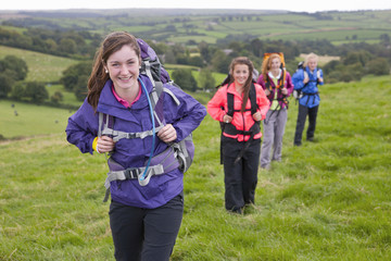 Portrait of girls with backpacks walking in field
