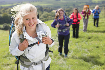 Portrait of smiling girls backpacking in field