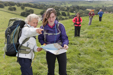 Girls with backpacks compass and map pointing in field