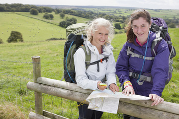 Portrait of smiling girls with backpacks compass and map against fence in field