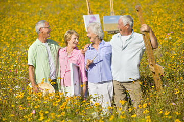 Smiling couples with paintings and easels among wildflowers in sunny meadow