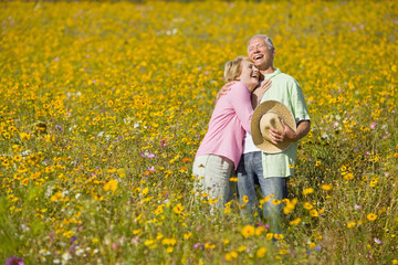 Smiling couple laughing and hugging among wildflowers in sunny meadow