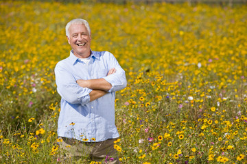 Portrait of smiling man standing with arms crossed among wildflowers in sunny meadow