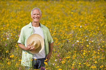 Portrait of smiling man holding hat among wildflowers in sunny meadow
