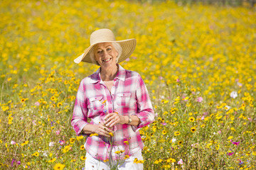Portrait of smiling woman among wildflowers in sunny meadow