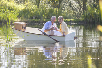 Portrait of smiling couple with wine glasses in rowboat on lake