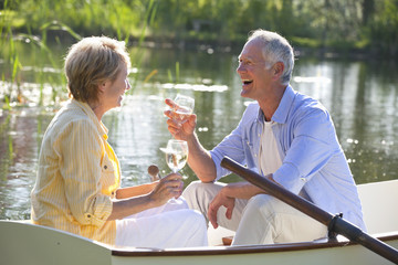 Smiling couple drinking wine in rowboat on lake