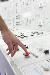 Man pushing red emergency button on control panel