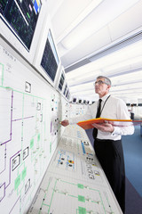 Engineer looking up at monitors in control room of nuclear power station