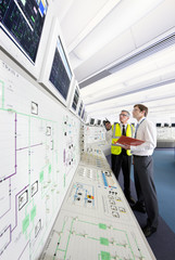 Engineers looking up at monitors in control room of nuclear power station