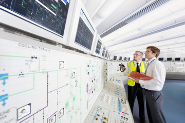 Engineers looking up at computer monitors in control room of nuclear power station
