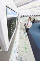 Engineer looking up at computer monitor in control room of nuclear power station