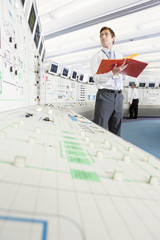 Engineer with binder looking up at computer monitor in control room of nuclear power station