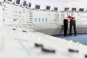 Engineers discussing paperwork in control room of nuclear power station