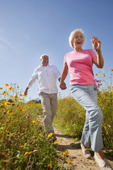 Enthusiastic senior couple running on path through sunny wildflower meadow