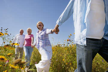 Enthusiastic senior couples running on path through sunny wildflower meadow