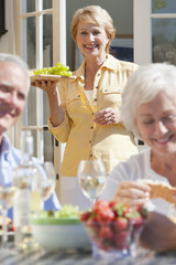 Smiling senior woman serving grapes on sunny patio
